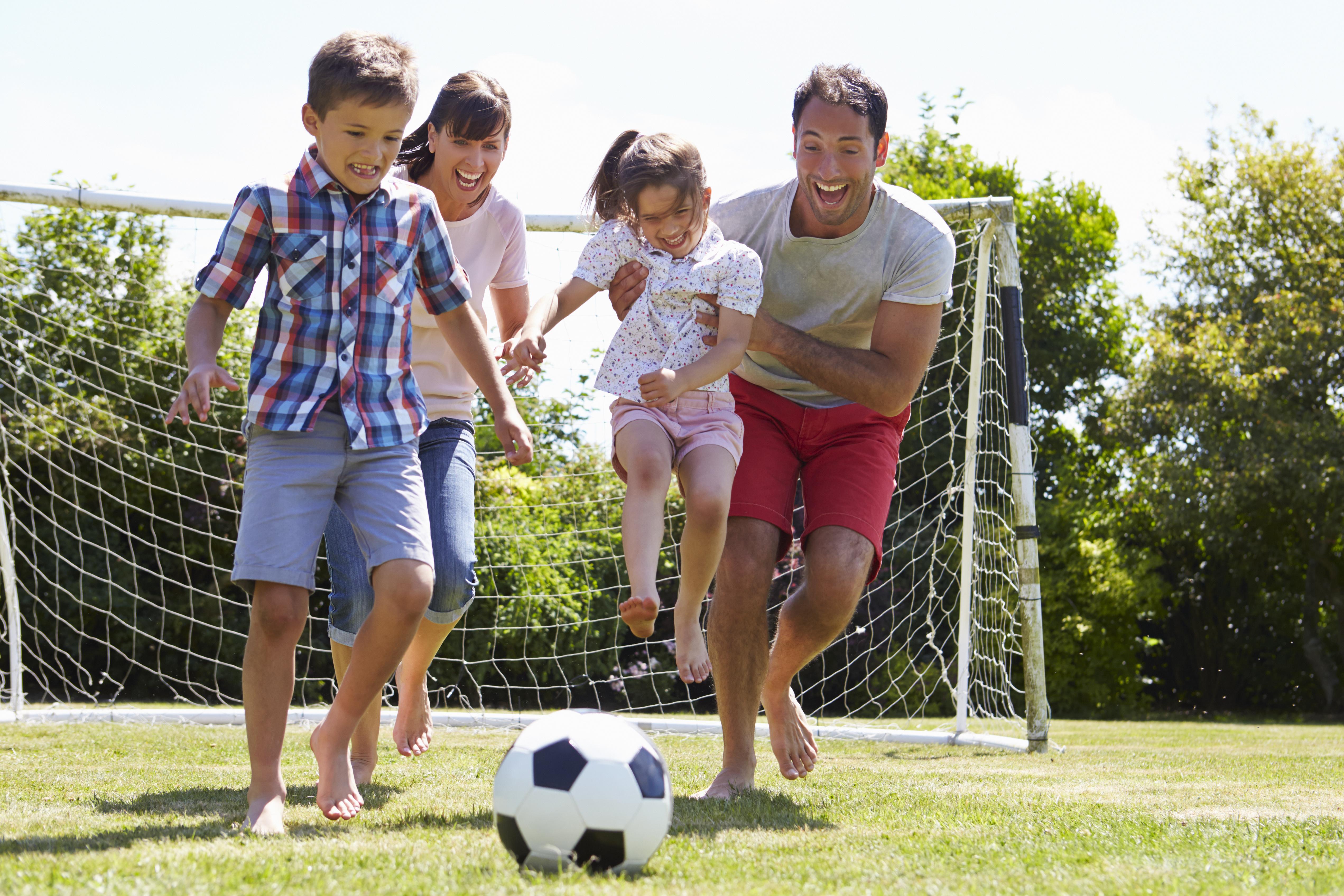 Familia jugando al fútbol en el jardín juntos