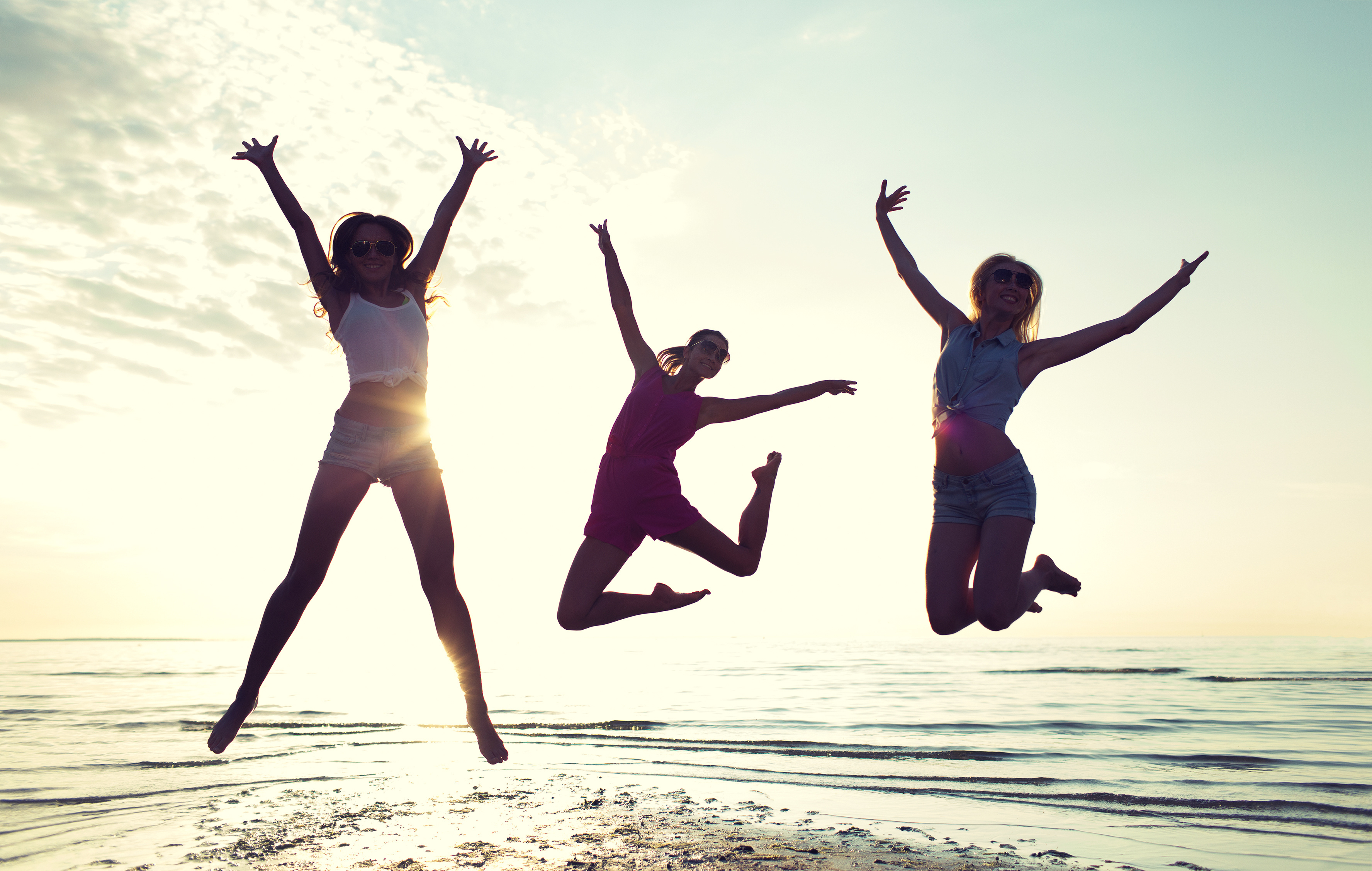 feliz amigas bailando y saltando en la playa